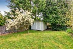 Il cortile recintato con erba ha riempito il giardino e la piccola tettoia immagine stock libera da diritti