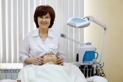 Il cosmetician sorridente fa al massaggio facciale paziente fotografie stock