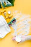 Il cosmetico dell'estate ha messo con la crema della protezione sulla vista superiore del fondo arancio Fotografia Stock Libera da Diritti