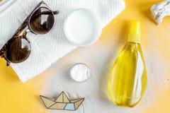 Il cosmetico dell'estate ha messo con la crema della protezione sulla vista superiore del fondo arancio Fotografia Stock