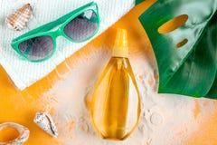 Il cosmetico dell'estate ha messo con la crema della protezione sulla vista superiore del fondo arancio Immagine Stock