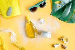 Il cosmetico dell'estate ha messo con la crema della protezione sulla vista superiore del fondo arancio Fotografie Stock