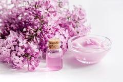 il cosmetico della stazione termale ha messo con il fondo bianco dello scrittorio dei fiori del lillà Fotografia Stock Libera da Diritti