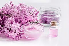 il cosmetico della stazione termale ha messo con il fondo bianco dello scrittorio dei fiori del lillà Fotografie Stock Libere da Diritti