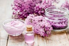 Il cosmetico della stazione termale ha messo con il fondo di legno dello scrittorio dei fiori del lillà Fotografie Stock