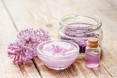 Il cosmetico della stazione termale ha messo con il fondo di legno dello scrittorio dei fiori del lillà Fotografia Stock Libera da Diritti