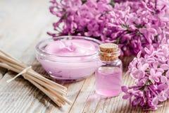 Il cosmetico della stazione termale ha messo con il fondo di legno dello scrittorio dei fiori del lillà Immagini Stock