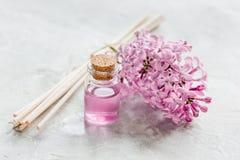 Il cosmetico della stazione termale ha messo con il fondo di pietra dello scrittorio dei fiori del lillà Immagini Stock Libere da Diritti