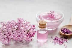 Il cosmetico della stazione termale ha messo con il fondo di pietra dello scrittorio dei fiori del lillà Fotografia Stock Libera da Diritti