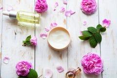 Il cosmetico screma ed olio rosa dell'essenza con i petali rosa sul trattamento bianco della stazione termale del fondo Massaggio Fotografia Stock Libera da Diritti