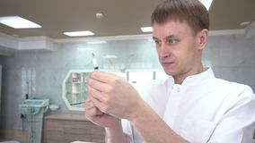 il cosmetologo che prende il farmaco in una siringa e la prepara per l'iniezione video d archivio