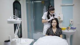 Il cosmetologo conduce la procedura per l'amministrazione della droga al cuoio capelluto stock footage