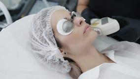 Il cosmetologo del movimento lento fa la procedura della ragazza per l'idratazione della pelle del fronte con il dispositivo spec archivi video