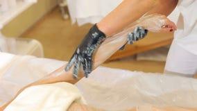 Il cosmetologo del primo piano applica una maschera d'idratazione sulla mano di una giovane donna stock footage