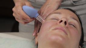Il cosmetologo fa il massaggio antinvecchiamento con le banche di vuoto Massaggio di fronte di vuoto per rigenerazione della pell video d archivio