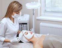 Il cosmetologo per la procedura di pulizia e di idratazione della pelle, applicante una maschera con il bastone al fronte di giov fotografia stock libera da diritti