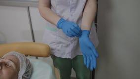 Il cosmetologo professionale indossa i guanti di gomma blu per la procedura archivi video