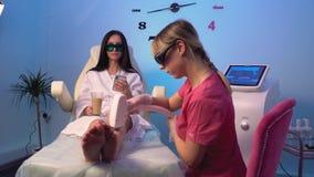 Il cosmetologo rende al paziente una procedura di depilazione del laser delle gambe video d archivio