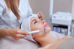 Il cosmetologo rende all'apparato una procedura della terapia di un bello, giovane donna di Microcurrent in un salone di bellezza immagine stock libera da diritti