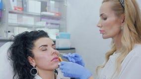 Il cosmetologo trasforma l'iniezione del botox la guancia stock footage