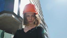 Il costruttore della ragazza con il hemlet sta stando con le armi attraversate di giorno di estate, il concetto di costruzione, c stock footage