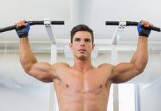 Il costruttore di corpo maschio senza camicia che fa la tirata aumenta fotografia stock