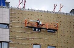 Il costruttore di lavoro è sull'elevatore e sugli impianti ad altezza quando finisce la costruzione Fotografia Stock Libera da Diritti
