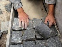 Il costruttore installa i mattoni di un granito sul percorso - una vista superiore fotografia stock