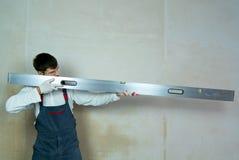 Il costruttore maschio imita una pistola con il righello della costruzione contro la parete vuota immagini stock libere da diritti