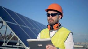 Il costruttore maschio sta stando accanto al pannello solare ed al lavoro Pannelli solari che raccolgono la luce di Sun stock footage