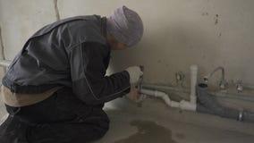 Il costruttore maschio in vestiti da lavoro fissa i tubi alla parete video d archivio
