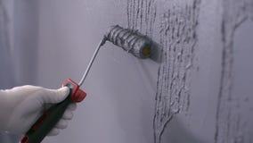 Il costruttore mette il gesso decorativo sulla parete immagine stock