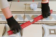 Il costruttore-muratore controlla il livello delle mattonelle orizzontali con Immagine Stock