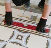 Il costruttore-muratore controlla il livello delle mattonelle orizzontali con Immagine Stock Libera da Diritti