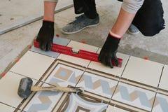 Il costruttore-muratore controlla il livello delle mattonelle orizzontali con Fotografie Stock Libere da Diritti