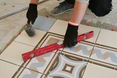 Il costruttore-muratore controlla il livello delle mattonelle orizzontali con Fotografia Stock Libera da Diritti