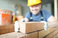 Il costruttore sorridente maschio mette per fare la muratura immagini stock libere da diritti
