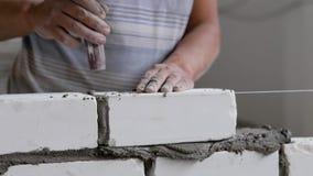 Il costruttore sta facendo la muratura, colpendo sopra il mattone dalla cazzuola per il livellamento ed il decollo del mortaio in stock footage