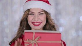 Il costume della donna di Santa tiene un regalo in sua mano ed ondeggia la sua mano, ciao Priorità bassa di Bokeh Fine in su archivi video