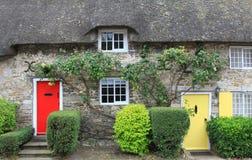 Il cottage con paglia ha ricoperto di paglia il tetto e le porte variopinte Fotografie Stock Libere da Diritti