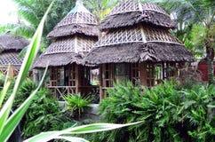 Il cottage delle foglie della noce di cocco e del bambù alloggia la linea in un parco a tema acquatico asiatico della giungla fotografia stock libera da diritti