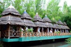 Il cottage delle foglie della noce di cocco e del bambù alloggia la linea in un parco a tema acquatico asiatico della giungla fotografie stock