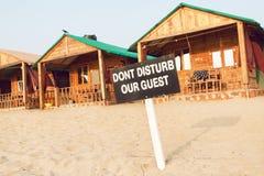 Il cottage e le cabine di legno della stazione balneare sabbiosa con il segno non disturbano i nostri ospiti Immagini Stock Libere da Diritti