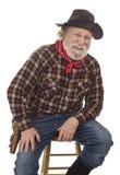 Il cowboy anziano allegro si siede su uno sgabello Fotografia Stock Libera da Diritti