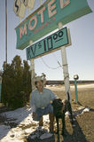 Il cowboy ed il suo cane si inginocchiano giù davanti al segno del motel delle sabbie con parcheggio di rv per $10, situato all'i Immagini Stock