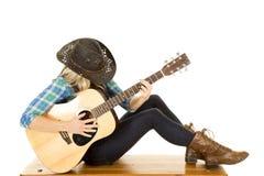Il cowgirl con la chitarra in camicia blu si siede le ginocchia Fotografia Stock