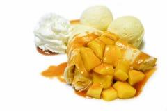 Il crêpe del mango con la salsa salata del caramello è servito con gelato alla vaniglia isolato con fondo bianco immagine stock libera da diritti