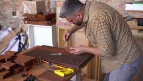 Il crafsman laborioso lavora alla piccola barca di legno archivi video