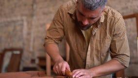 Il crafsman laborioso lavora alla piccola barca di legno video d archivio
