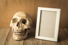 Il cranio ed il legno incorniciano la natura morta su fondo di legno Fotografia Stock
